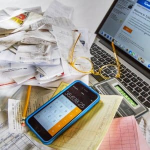 receipts, smartphone, pencl and a laptop