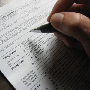 hand with pen filling out federal tax return 1040 form
