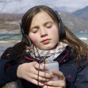 teen girl listening to music through headphones (Photo by iStock)