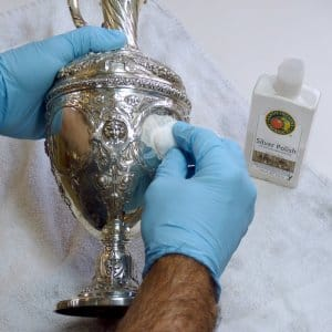 Hands polishing a silver goblet