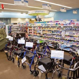 aisle lined with walkers, lift chairs, first aid producs on shelves inside a retail pharmacy store.
