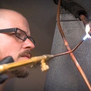 HVAC technician brazing copper