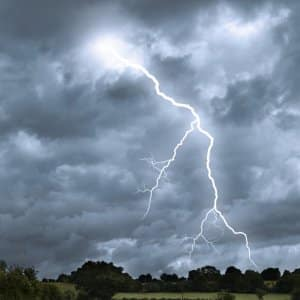 lightning strikes from a stormy sky over a countryside landscape