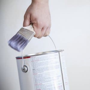 someone carrying a paint can and paint brush