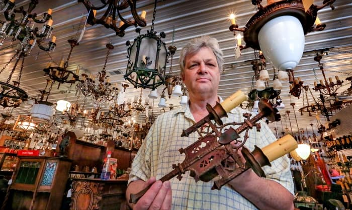 antique store owner holding a light fixture (Photo by Frank Espich)
