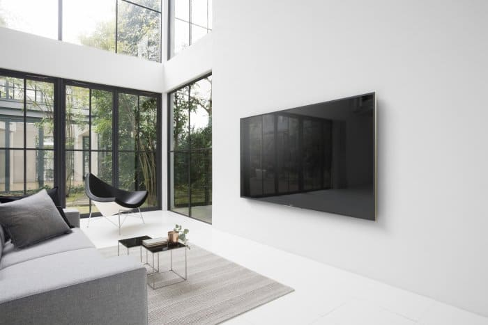 "Lifestyle shot of a Sony 65"" ZD9 4K Ultra HD TV with High Dynamic Range (HDR) wall mounted in a living room."