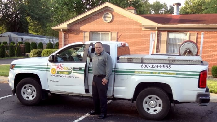 man standing in front of his company truck