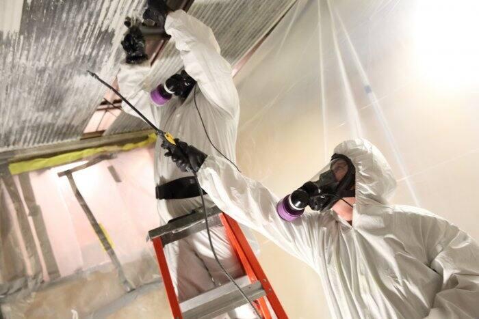 men wearing white suits, masks, removing asbestos