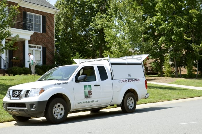 pest control technician spraying house with company truck in front