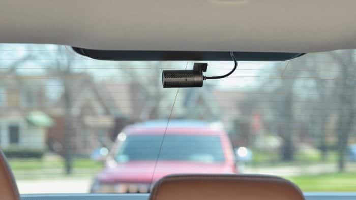 Lifestyle shot of a Cobra CDR 895 dash cam, rear camera mounted and looking out the back window while driving.