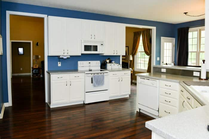 Kitchen with white cabinets and blue walls.