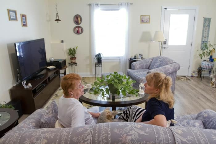 two women sitting on couch in remodeled apartment