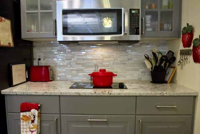 Red pot on a cooktop in a renovated basement apartment.