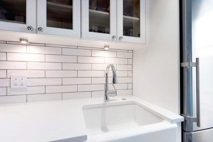 White cabinets and counters with subway tile and apron sink