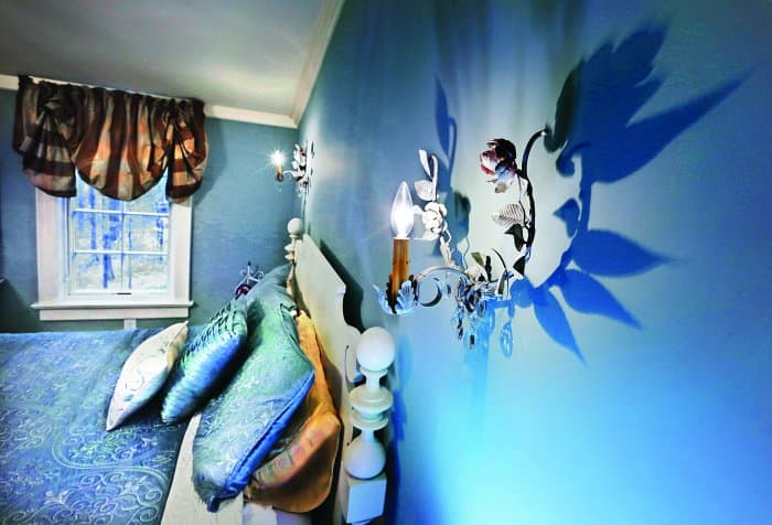 blue bedroom with wall sconces