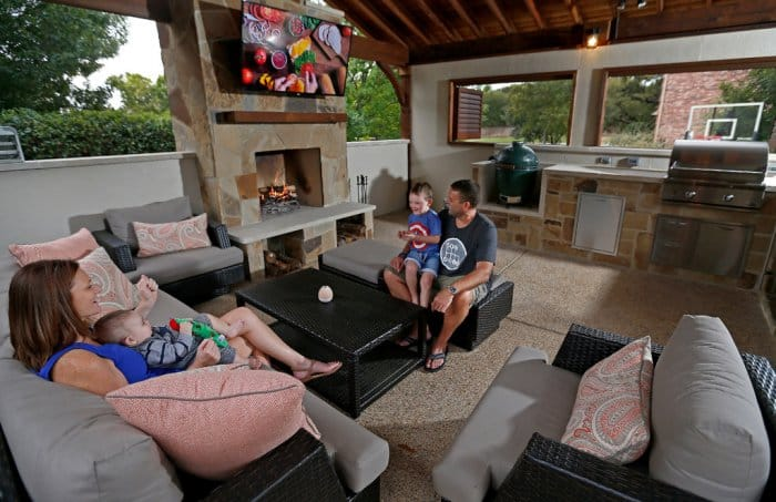 A family of four outside in their outdoor kitchen