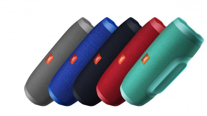 Product shot of four JBL Charge 3 waterproof Bluetooth speakers, one each in grey, blue, black, red and teal.
