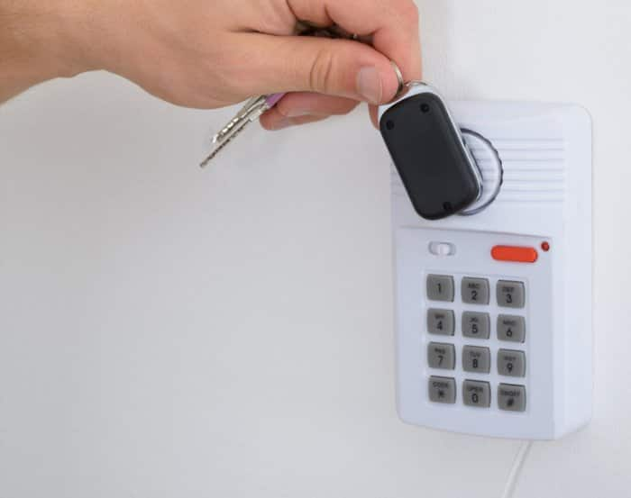 man holding key fob to communicate with house alarm