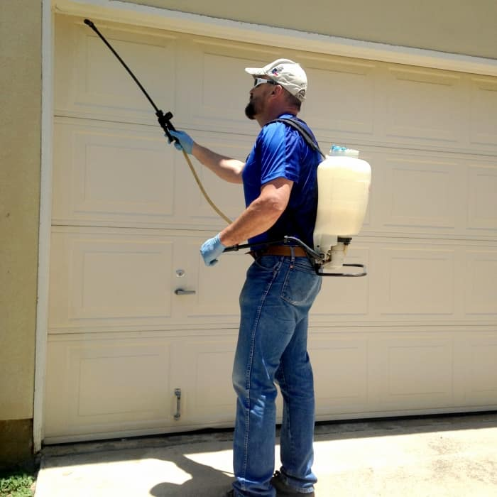 technician spraying garage for pests