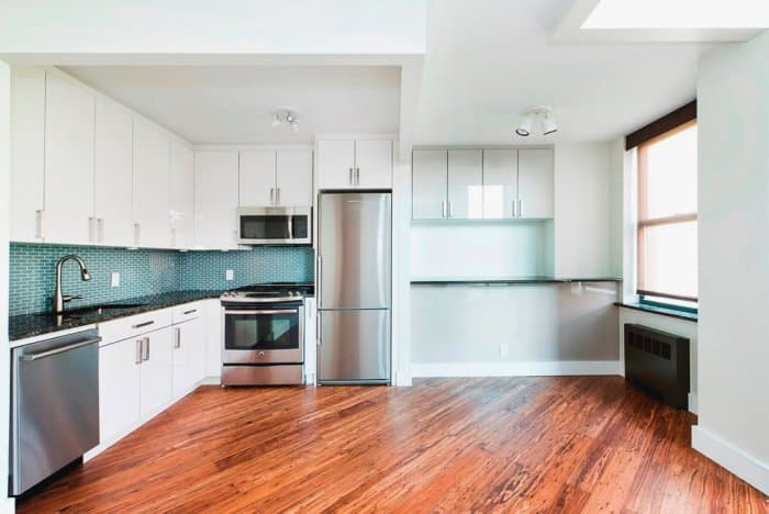 White Kitchen Cabinets With Stainless Steel Appliances. Laminate Flooring  ...