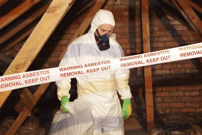 man in haz-mat suit removing asbestos behind warning sign