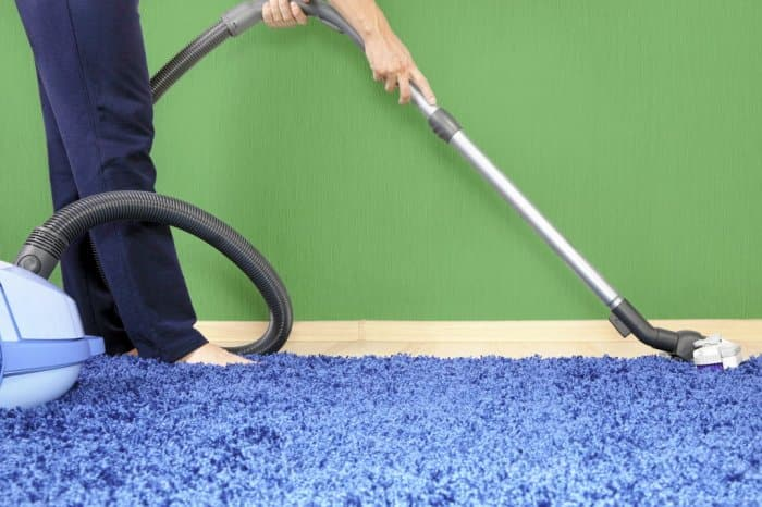 Someone running a vacuum cleaner on blue carpet