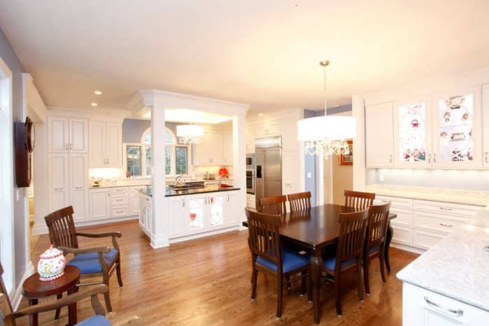 White kitchen with wood floors and table.
