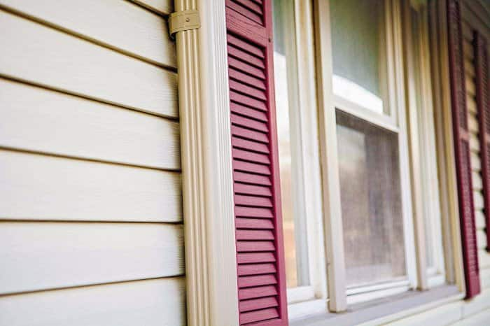 Tan vinyl siding an red shutters on a house