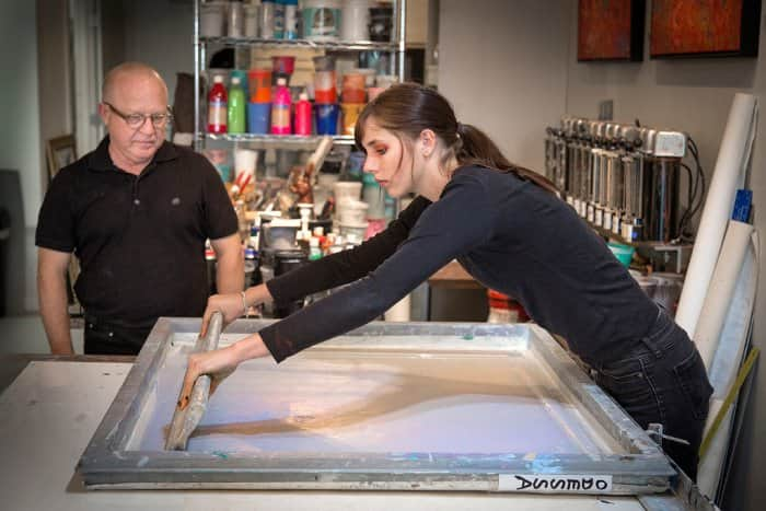 Emily McAvoy assists artist Walter Knabe with screen printing at his South Broad Ripple studio