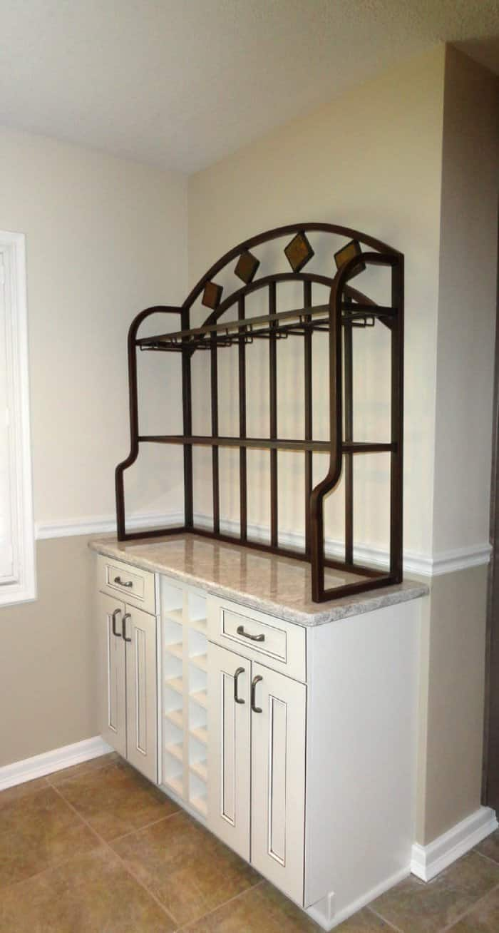 A custom wine rack with white cabinets and quartz countertops