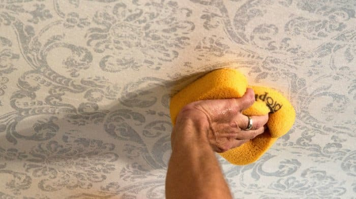 Walter Knabe custom wallpaper being affixed to his dining room ceiling