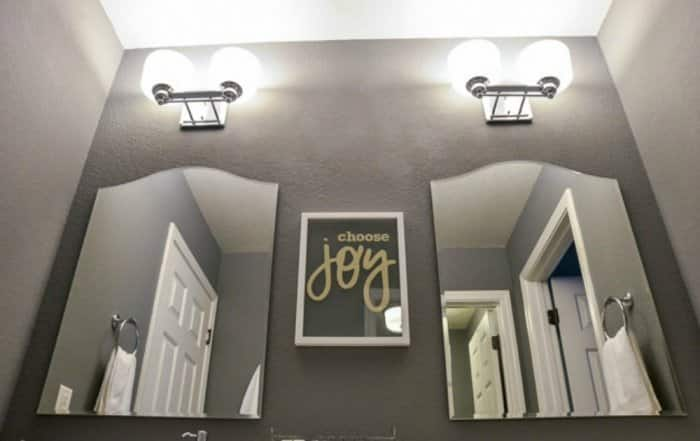 beveled mirrors with chrome light fixtures above in bathroom