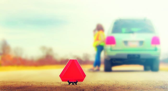 triangle emergency sign in front of broken down car