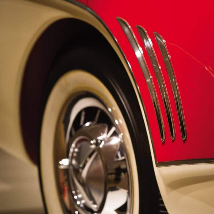 closeup of the tire on a rare red and cream concept car with white wall tires on chrome