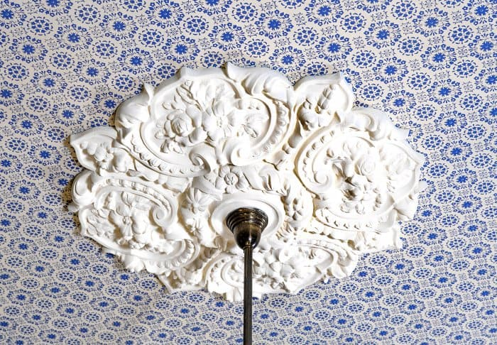ceilihng medallion surrounded by blue and white wallpaper (Photo by Frank Espich)