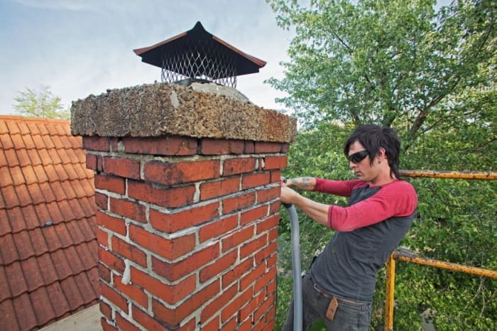 A contractor repairs the brick work on a chimney