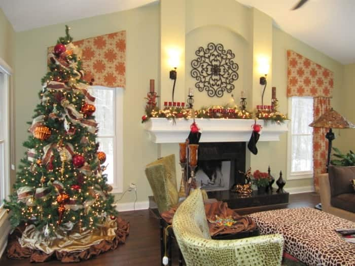 holiday-decorated living room with tree and mantel