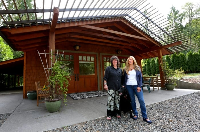 two women and dog posing in front of transformed pole barn