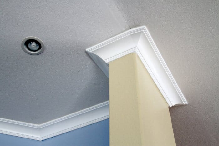 White crown molding on an angled and textured white ceiling, top of a light blue wall and beige wall visbile, recessed light in shot