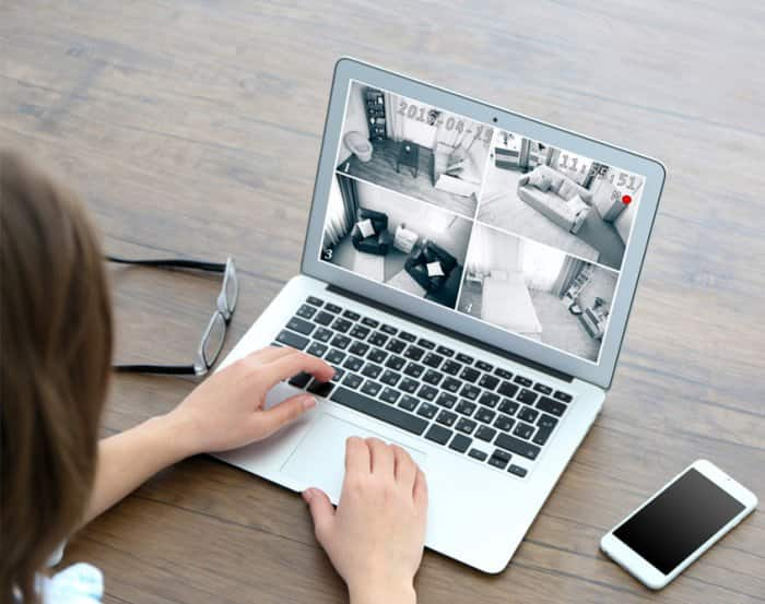 woman viewing home security video on laptop computer