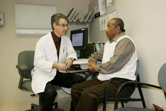 senior man talks with doctor in white coat at doctor's office.