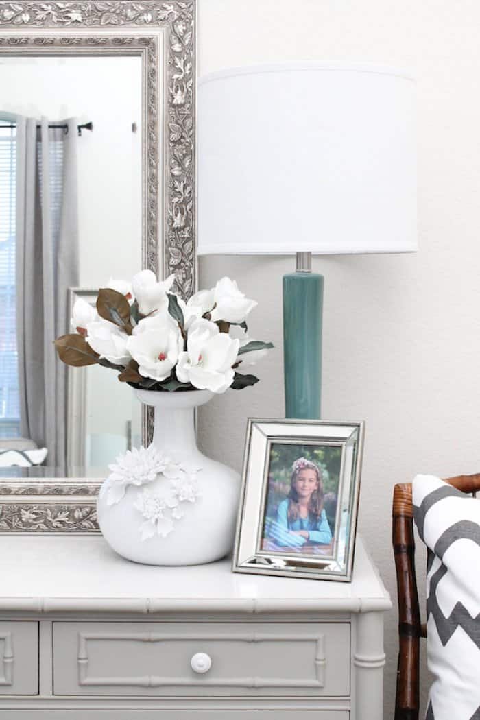 dresser tops with lamp, flowers, and photo of child