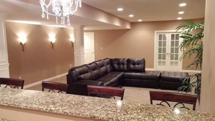 finished basement with leather sectional, wall sconces and bar