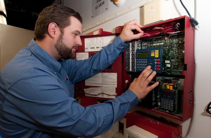 professional security technician inspecting fire alarm