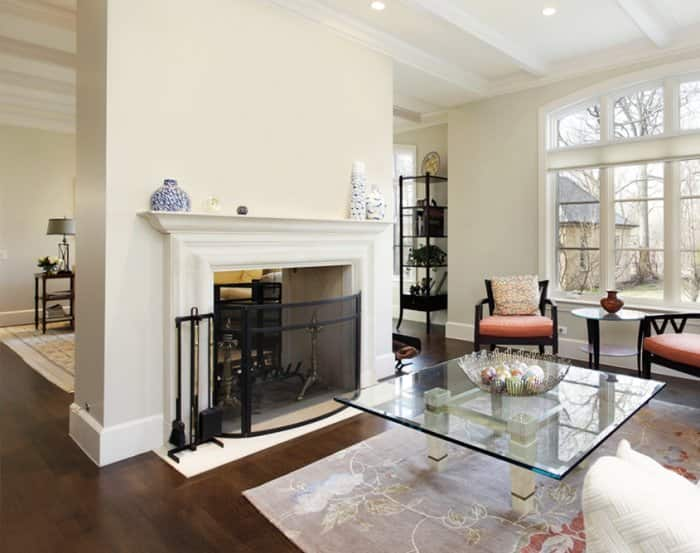 White fireplace mantel with black fire screen