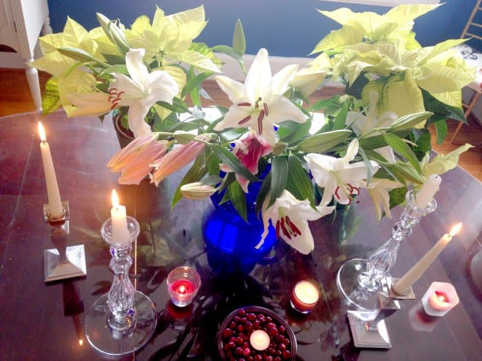 flowers in 3 vases and lit candles on table