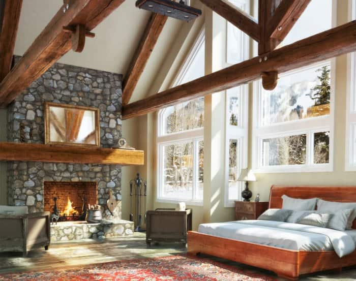 Stone fireplace in bedroom with high ceiling