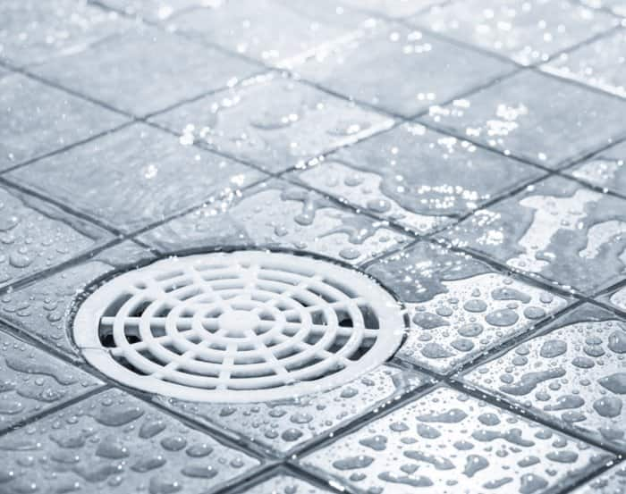 Close up of plastic drain embedded in shower tiles