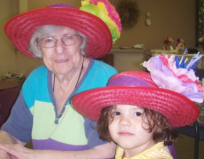 senior woman playing dress up with female child