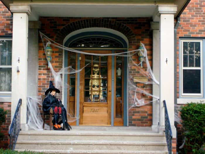 Halloween porch with cobwebs, skeleton and witch